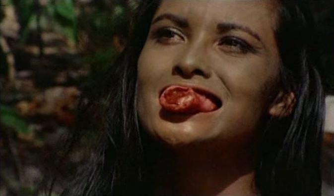 """""""褐色のエマニエル""""ことラウラ・ジェムサーが、男性器を食いちぎる衝撃的な残酷描写。廃屋でゾンビの群れを撃退したジョンは、浜辺に居た娘に迫るが性器を食いちぎられ絶命、追ってきたゾンビたちに喰われてしまう。"""