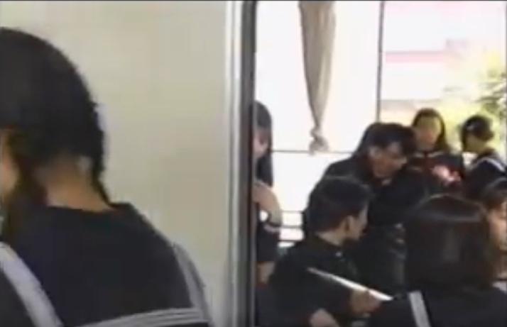 (画面真ん中ほどに)教室から半分だけ顔を出している「謎の少女」が映っている。無表情で不自然にカメラのほうをじっと見つめている姿はとても不気味である。