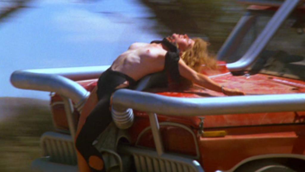 ジェシカがおっぱいを丸出しにされて車に縛りつけられる磔のシーン。磔のまま車を走らせジェシカは気絶してしまう胸糞悪い展開。
