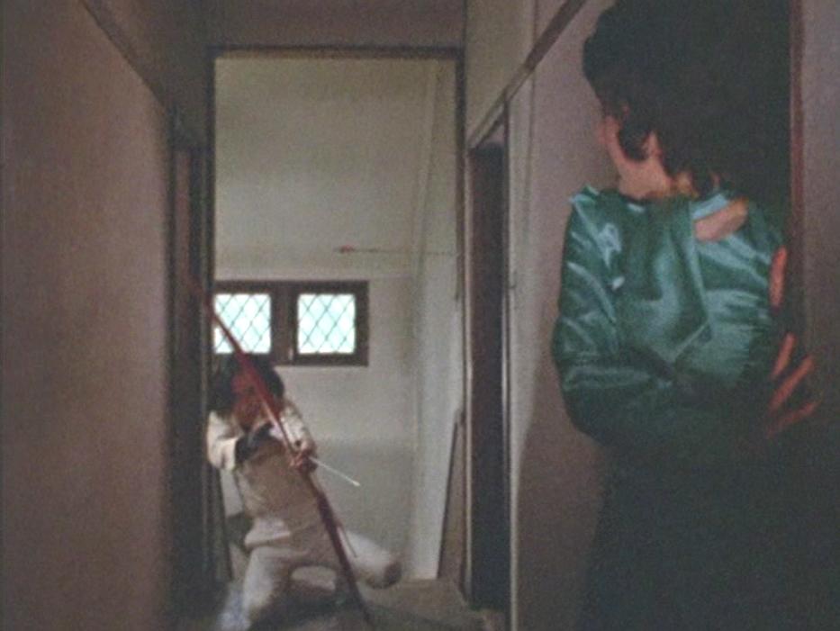 久里がいない間になんとか逃げ出そうとする美川隊員だったが、見つかってアーチェリーで追い詰められる。