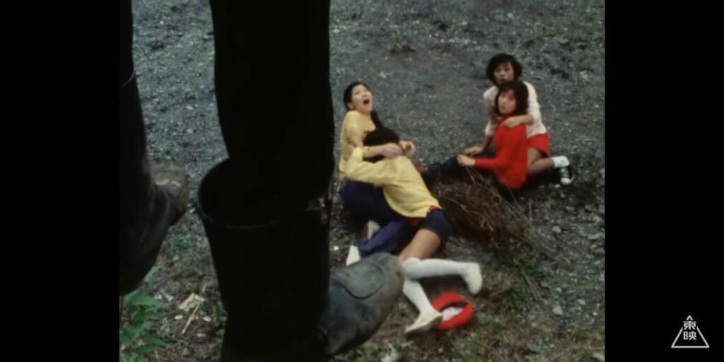 首を吊っているショッカー戦闘員の遺体を見上げて、悲鳴を上げるライダーガールズの女性たち。