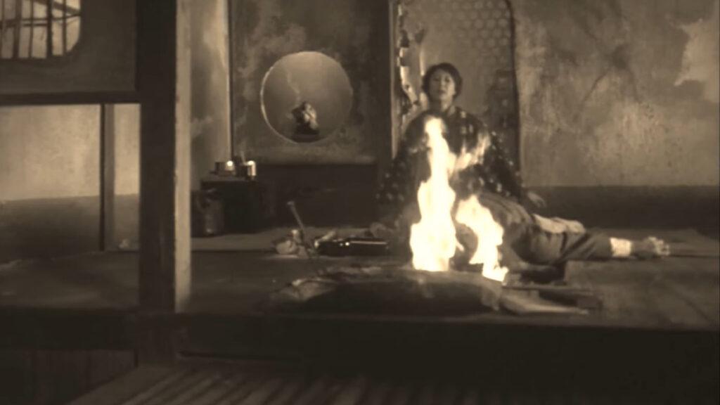 リカに薪で後頭部を殴られて前に倒れた源治郎は、そのまま囲炉裏の炎に顔を突っ込んだ…。