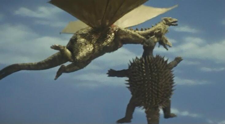 キングギドラは、アンギラスを首に噛みつかせたまま飛び上がり、空中から落としたうえで踏みつけたりして奮戦する