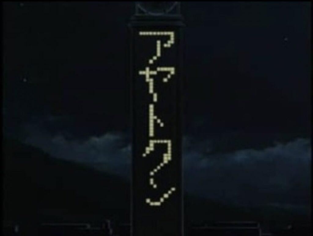 戦いの最中、夜の街のネオンに文字が浮かび上がる。